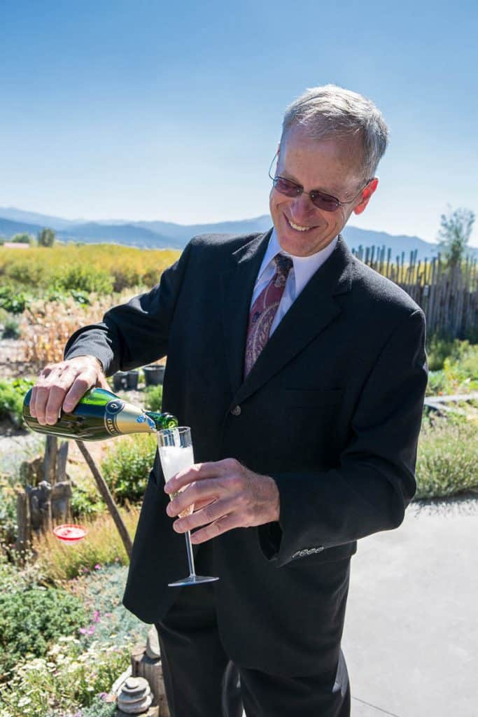 New Mexico wedding officiant Dan Jones pouring the couple a glass of champagne after the ceremony.