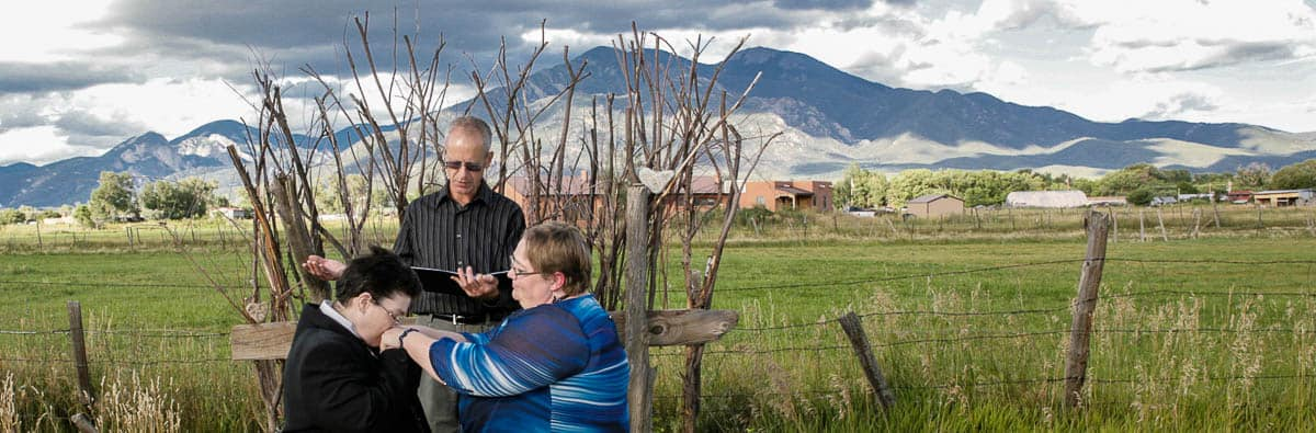 A couple exchange vows with the mountains of Taos, New Mexico in the background.