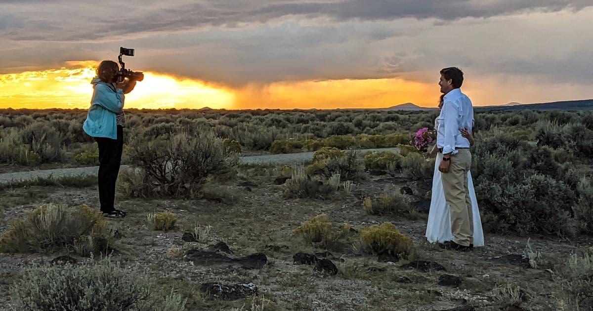 A photographer takes a formal photos at a couple's wedding elopement