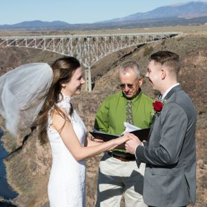 a bride's veil blows in the breeze as she says her vows at the Rio Grande gorge