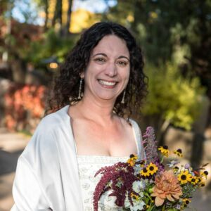 A happy bride holding a bouquet of flowers from the Spirtaos Gardens