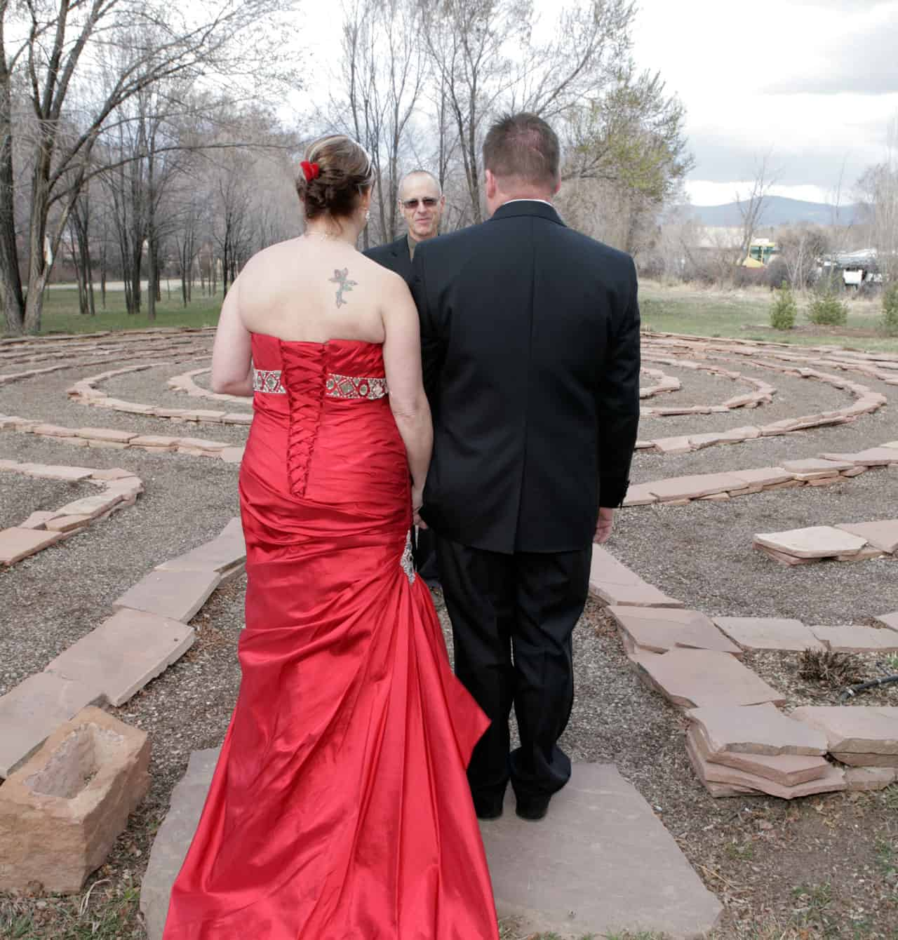 A wedding outdoors where the bride is wearing a red dress for her Christmas wedding.