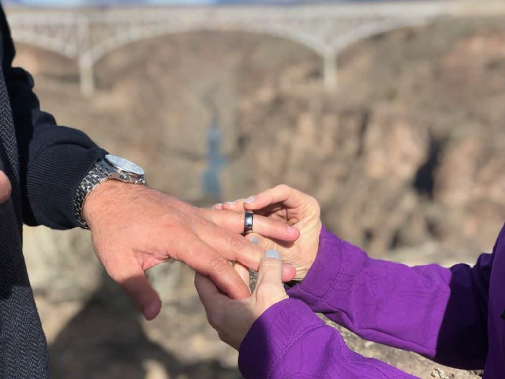 The thread of the Rio Grande River is the backdrop as she places his ring on his finger.